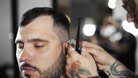 Il barbiere di Tattoed fa il taglio di capelli per il cliente al negozio di barbiere usando il hairclipper, il taglio di capelli  stock footage