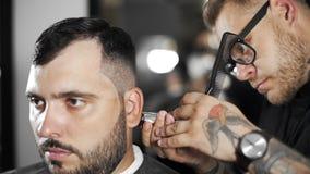 Il barbiere di Tattoed fa il taglio di capelli per il cliente al negozio di barbiere usando il hairclipper, il taglio di capelli  video d archivio