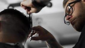 Il barbiere di Tattoed fa il taglio di capelli per il cliente al negozio di barbiere usando le forbici e pettine, taglio di capel video d archivio