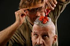 Il barbiere dipinge con pittura rossastra di un cittadino dai capelli grigi anziano immagine stock