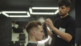 Il barbiere fa i capelli che disegnano con la lacca per capelli dopo il taglio di capelli al negozio di barbiere Giovane uomo cau archivi video