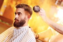 Il barbiere fa un taglio di capelli per un giovane uomo bello con una barba ed i baffi immagini stock