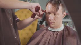 Il barbiere maschio fa il taglio di capelli con il rasoio elettrico, al rallentatore archivi video