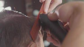 Il barbiere maschio fa il taglio di capelli con il rasoio elettrico, al rallentatore stock footage