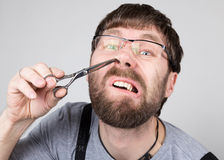 Il barbiere maschio taglia i suoi propri capelli nel naso, esaminante la macchina fotografica come lo specchio parrucchiere profe fotografie stock