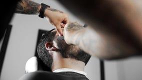 Il barbiere rade il cliente con la lametta diritta, il taglio di capelli del ` s dell'uomo e la rasatura al parrucchiere, al nego video d archivio