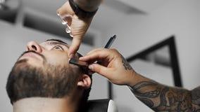 Il barbiere rade il cliente con la lametta diritta, il taglio di capelli del ` s dell'uomo e la rasatura al parrucchiere, al nego archivi video