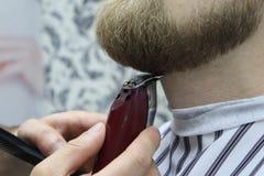 Il barbiere rade la barba dell'uomo del cliente sul parrucchiere della sedia Taglio di capelli della barba barbiere che rade barb fotografia stock