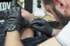 Il barbiere rade la barba di un uomo anziano con il rasoio tagliente dei capelli grigi fotografia stock