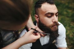 Il barbiere rade un uomo barbuto immagine stock libera da diritti