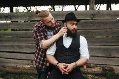 Il barbiere rade un uomo barbuto fotografia stock libera da diritti