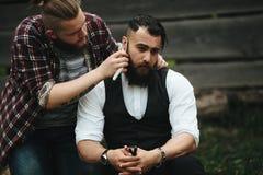 Il barbiere rade un uomo barbuto fotografia stock