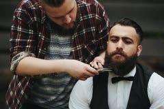 Il barbiere rade un uomo barbuto all'aperto fotografie stock libere da diritti