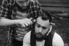 Il barbiere rade un uomo barbuto all'aperto fotografia stock libera da diritti