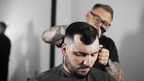 Il barbiere sbatte i capelli via tosati dalle spalle del ` s del cliente dalla spazzola, barbiere tattoed fa il taglio di capelli stock footage