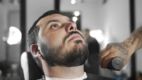 Il barbiere sbatte i capelli via tosati dalle spalle del ` s del cliente dalla spazzola, barbiere tattoed fa il taglio di capelli video d archivio