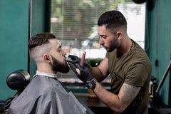 Il barbiere sistema i baffi dell'uomo alla moda moro ad un parrucchiere fotografia stock libera da diritti