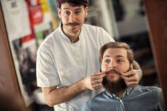 Il barbiere sorridente dell'uomo sta servendo il cliente fotografia stock