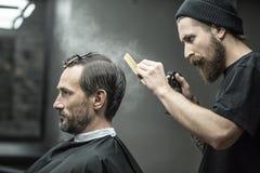 Il barbiere sta utilizzando la bottiglia dello spruzzo immagine stock