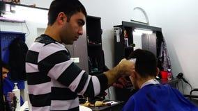 Il barbiere taglia i capelli del cliente con il tagliatore in un parrucchiere archivi video