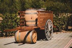 Il barilotto di legno con rosso e il wihte wine per avere un sapore in carretto sulla vigna Oggetto strutturato immagine stock
