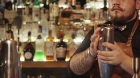 Il barista adulto alla moda sta scuotendo il cocktail in un agitatore, stante dietro la barra stock footage