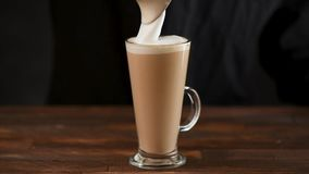 Il barista aggiunge la schiuma cotta a vapore del latte a caffè archivi video