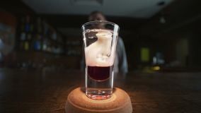 Il barista aggiunge il sirop di gemito al colpo stratificato con liquore e gin rossi al rallentatore, facendo i cocktail in una b stock footage