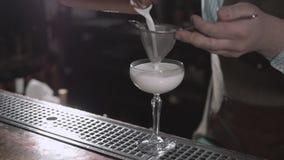 Il barista che prepara il coctail con l'attrezzatura della barra, setaccio del tiro e la spruzza stock footage