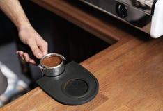 Il barista che tiene il portafilter con caffè macinato sopra tamp la stuoia al contatore della barra, primo piano fotografie stock