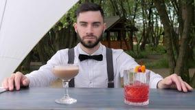 Il barista del ritratto dietro la barra, baristi presenta l'alcool, il primo piano del barista, bevande raffreddate colorate sul  archivi video