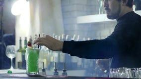 Il barista del tipo mette le paglie di plastica in cocktail variopinto con le bacche sullo scaffale stock footage