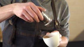 Il barista dell'uomo ha versato in una cannella della tazza di caffè in una caffetteria moderna stock footage