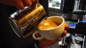 Il barista estrae il latte sopra un caffè stock footage