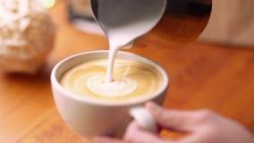 Il barista estrae il latte sopra un caffè - fare l'arte del latte per cappuccino Barista che fa dell'arte del latte del caffè, fo archivi video