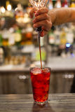 Il barista fa un cocktail rosso immagini stock