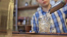 Il barista getta su un vetro di cocktail, messo sul contatore della barra ed aggiunge il ghiaccio, rallentatore video d archivio
