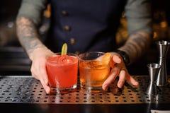 Il barista ha preparato per i cocktail della barra due di rosso e di arancio fotografia stock