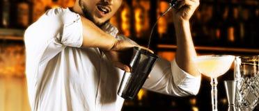 Il barista incendiario meravigliosamente versa l'alcool dal bott Immagini Stock