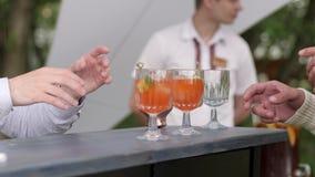 Il barista incita il cliente ad assegnare le bevande, barista decora il coctail, barista fa il cocktail di colore, tapster dietro video d archivio
