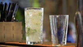 Il barista mescola il cocktail con il cucchiaio ed ha messo due tubi dentro il vetro video d archivio