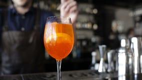Il barista mescola gli ingredienti nel vetro Bastoni e paglie del cocktail nel vetro archivi video