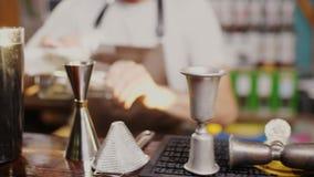 Il barista, nel defocus del contatore della barra, sfrega il vetro stock footage