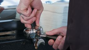 Il barista preme il caffè macinato facendo uso del compressore