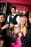 Il barista prepara gli amici dei cocktail che bevono alla barra Immagine Stock