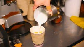 Il barista prepara il latte dentro porta via la tazza caffè - effetto del latte archivi video