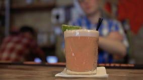 Il barista presenta il cocktail esotico decorato con una calce archivi video