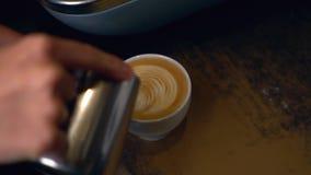 Il barista produce il Latte del caffè con una forma del cuore nella schiuma per il giorno di biglietti di S. Valentino archivi video