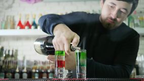 Il barista professionale prepara il cocktail colorato e versa scozzese luminoso dalla bottiglia in vetro con l'alcool sulla barra archivi video