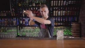 Il barista professionista mescola un cocktail in una condizione dell'agitatore sul contatore della barra sui precedenti delle bot video d archivio
